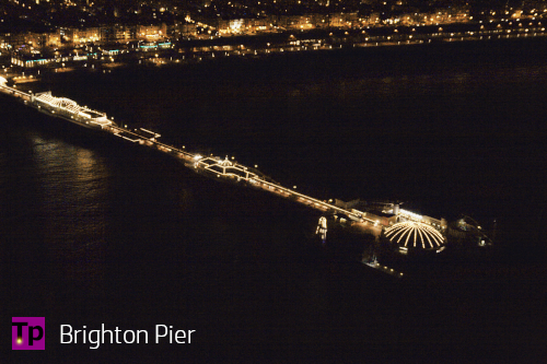 Brighton Pier, England. Lights at night from a seaside town reflect of the water.